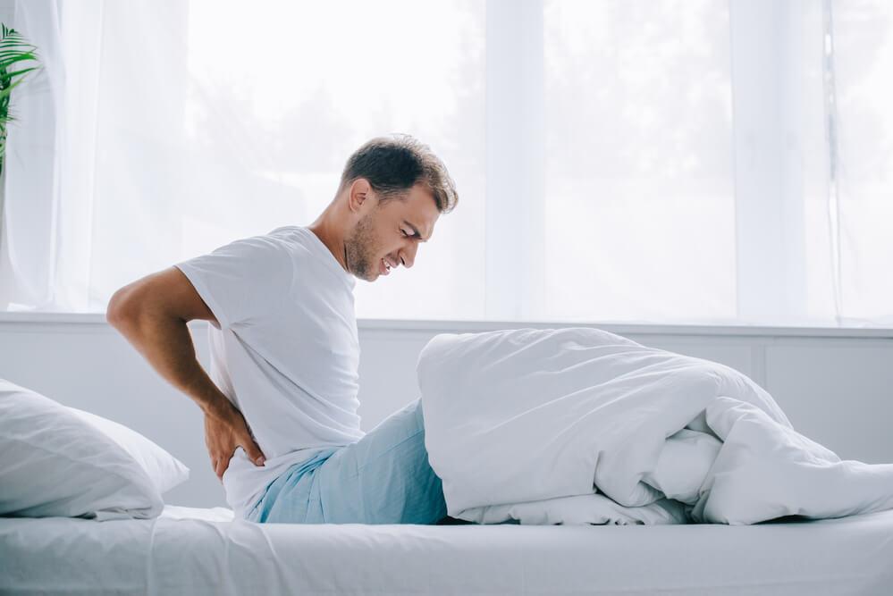 mężczyzna wstający z łóżka z bólem pleców