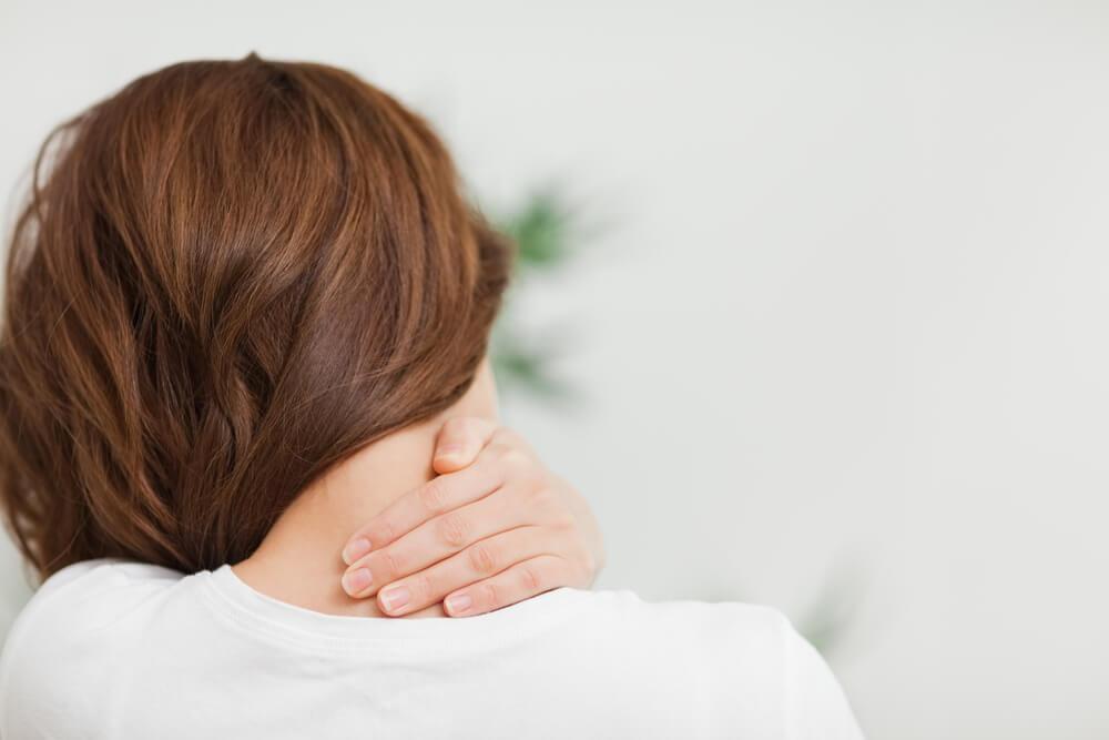kobieta dotyka karku